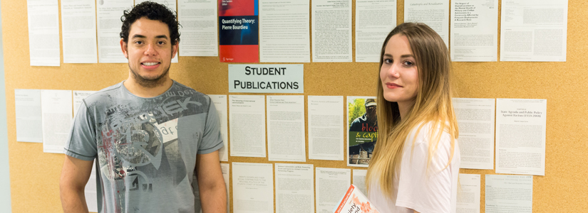 photo of two students in front of the student publications bulletin board